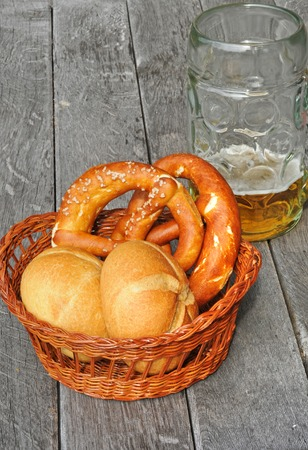 bap: Basket with bread rolls and pretzels on an old table
