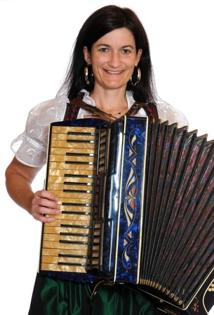 aerophone: Woman in bavarian dirndl with accordion in front of a white background Stock Photo