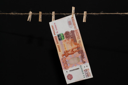 greenback: greenback of 5000 ruble on hemp rope with wooden clothespin Stock Photo