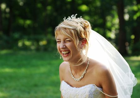 Bride laughing expressively on the meadow during the photo session. Stock Photo