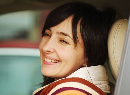 Beautiful brunette woman laughing while driving the car with leather chairs photo