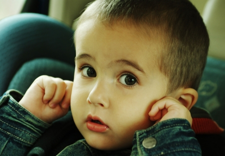 noise: Boy stops up his ears with fingers avoiding loud sound of traffic in the car Stock Photo
