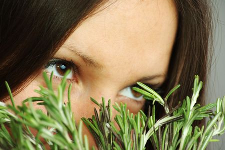 Beatutiful girl with bright eyes sniffing rosemary