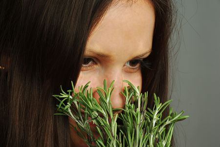 Beatutiful girl with bright eyes sniffing rosemary photo