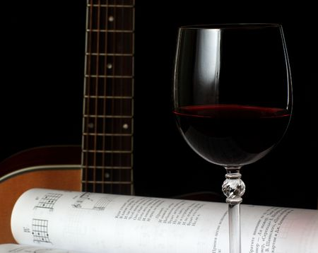 Wineglass and guitar and music notes on white background