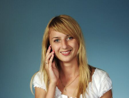 Beautiful blonde girl talking by mobile phone photo