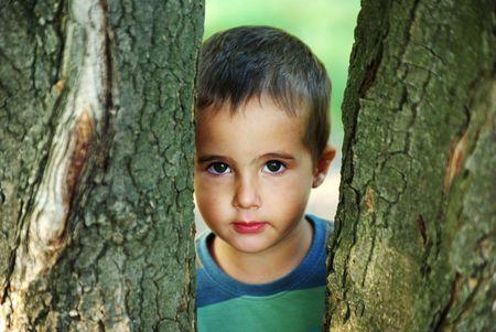 Nice boy hiding behind the big trees