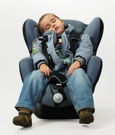 Boy sleeps in safe auto chair isolated on grey background