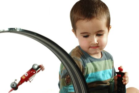 Boy plays toy car racing system and fails to pass the turn photo