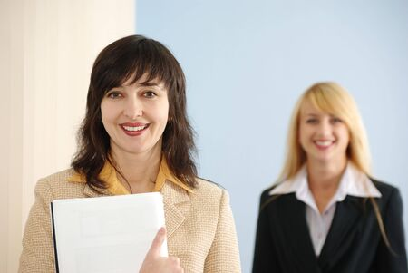 Brunette girl holding the plain covered book while blonde is approaching photo