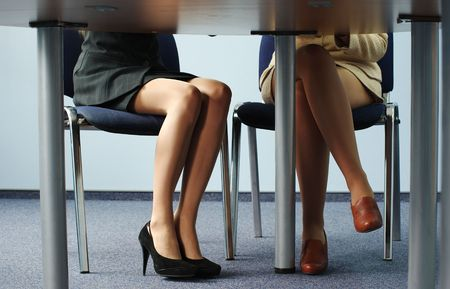 legs heels: Legs of two businesswomen under the meeting room table Stock Photo
