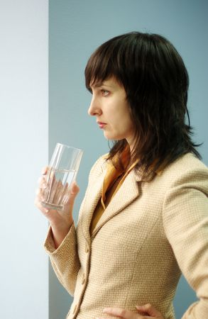 Beautiful brunette woman in yellow suite with glass of water by the window in the office photo