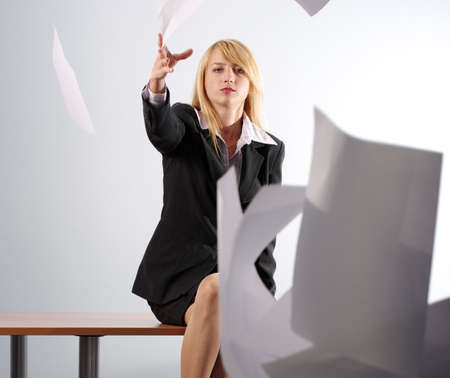 Angry blonde girl throwing white sheets of paper sitting on the desk in the office photo