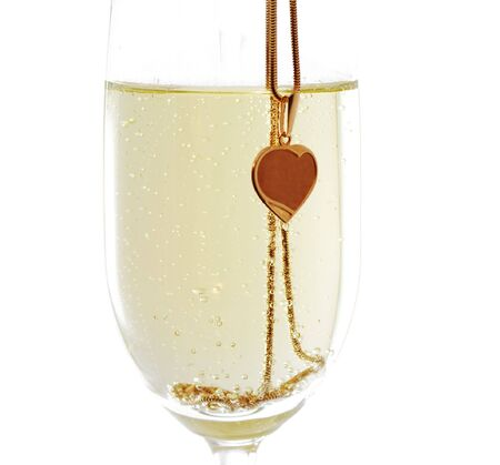 Closeup of wineglass with sparkling wine and golden heart on the golden chain, isolated on white photo