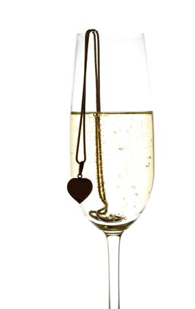 Closeup of wineglass with sparkling wine and golden heart on the golden chain in high key, isolated on white photo