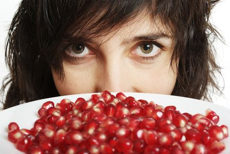 pomegranate juice: Face closeup of beautiful woman holds pomegranate berries in white plate, isolated on white