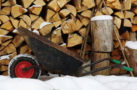 Old wheelbarrow with the red wheel on firewood stack background photo