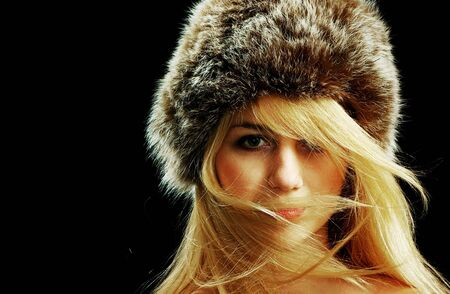 Beautiful blonde in fur hat with naked shoulders, isolated on black photo