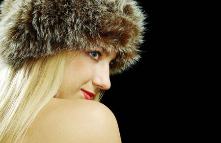 Beautiful blonde in fur hat with naked shoulders, isolated ob black photo