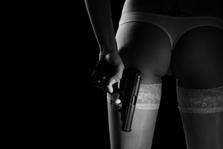Sexy girl hiding the gun behind back, isolated on black Stock Photo