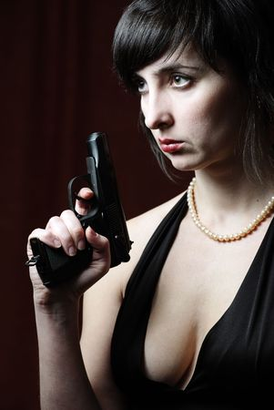 Woman in evening dress and pearl necklace holds gun