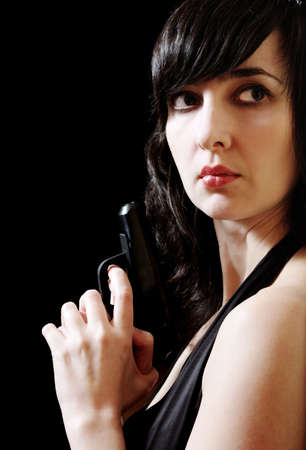 Woman in evening dress holds gun looking around the corner photo