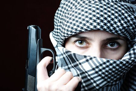 Arab woman eyes in keffiyeh with gun