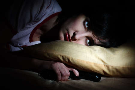 Women awoke of sudden noise with the gun under the pillow Stock Photo