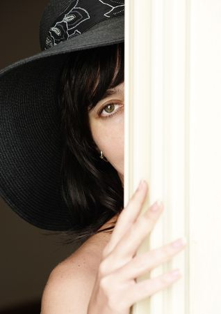 Beautiful brunette woman in black hat with naked shoulder looking fro behind a curtain Stock Photo - 6637405
