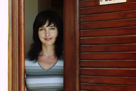 Beautiful woman welcomes at the wooden door Stock Photo