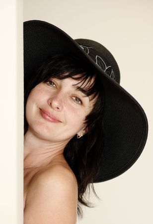 Beautiful brunette woman in black hat with naked shoulder looking from behind a corner Stock Photo - 6676446
