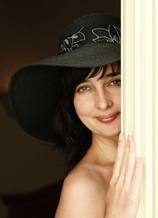 Beautiful brunette woman in black hat with naked shoulder looking from behind a curtain photo