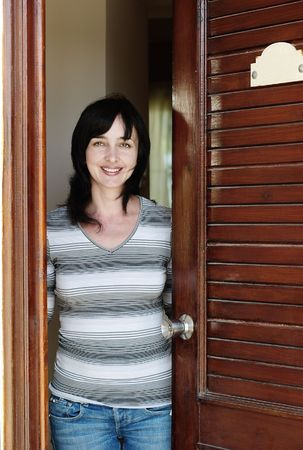 Beautiful woman in jeans welcomes at the wooden door Stock Photo - 6676451