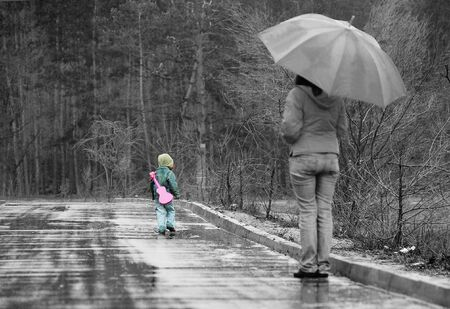 Little boy runs away from his mom by rainy road, grayscale with highlighted boy