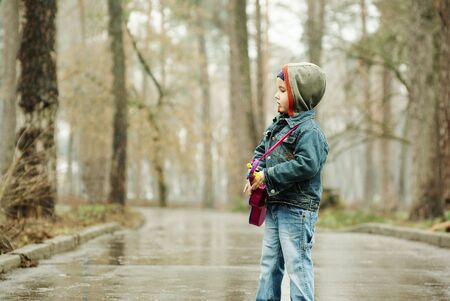 Little boy plays guitar in rainy park Stock Photo - 6747327