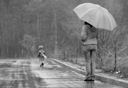 Mother wathces as her son goes away in a stormy weather Stock Photo