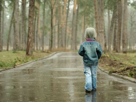 Little boy walks the long rainy road in the forest