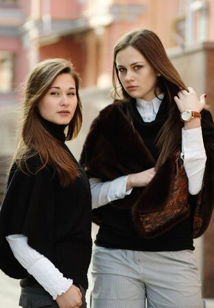 Two beautiful brunette girls in fashion clothes in the downtown Stock Photo - 6788769