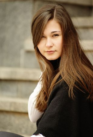 Portrait of young woman with long hair sitting on the stairs Stock Photo - 6788778