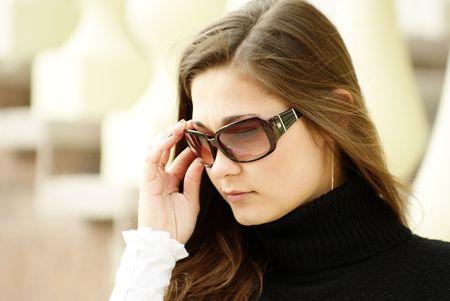 Beautiful yong girl in sunglasses by balustrade photo