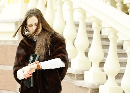 stole: Woman in fur stole looks at her watch by balustrade