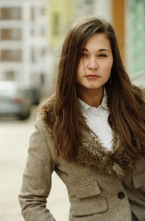 Portrait of young woman in jacket with fur collar outdoors photo