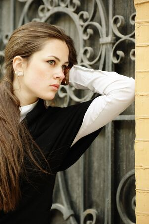 Beautiful girl portrait by the forged gates photo