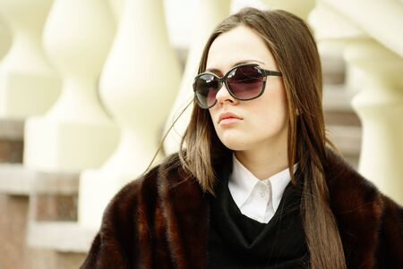 Beautiful young woman in sunglasses by balustrade photo