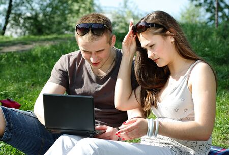 Young couple with laptop in the park on the spring meadow photo