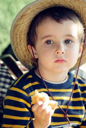Small boy in straw hat daydreams on the sun with a pie in hand Stock Photo - 6956998