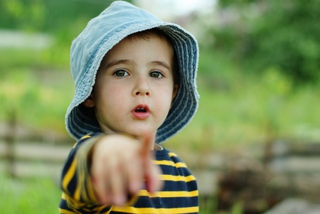 Little boy in jeans hat points to the camera outdoors Stock Photo - 7014558