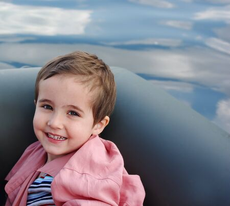 Little boy in the inflatable boat with clouds reflected in the river photo