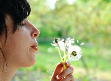 Woman blows up dandelion backlit with the sun photo