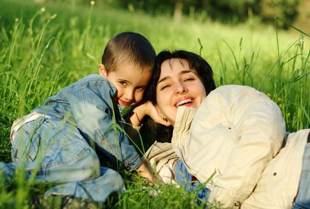 Mother and son outdoors lying on the grass photo